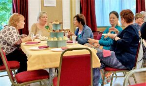 women sitting at tables having tea and cakes