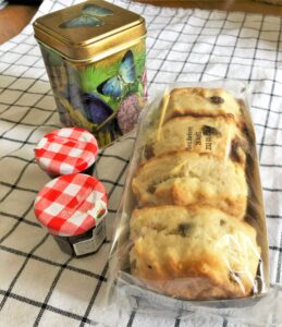four scones and two jars of jam, and a tin of tea